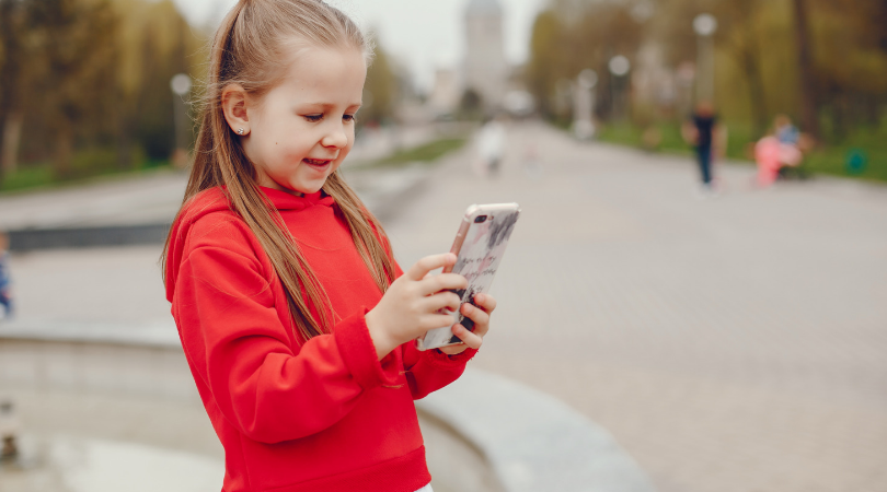 dziewczynka trzyma telefon komórkowy i coś czyta